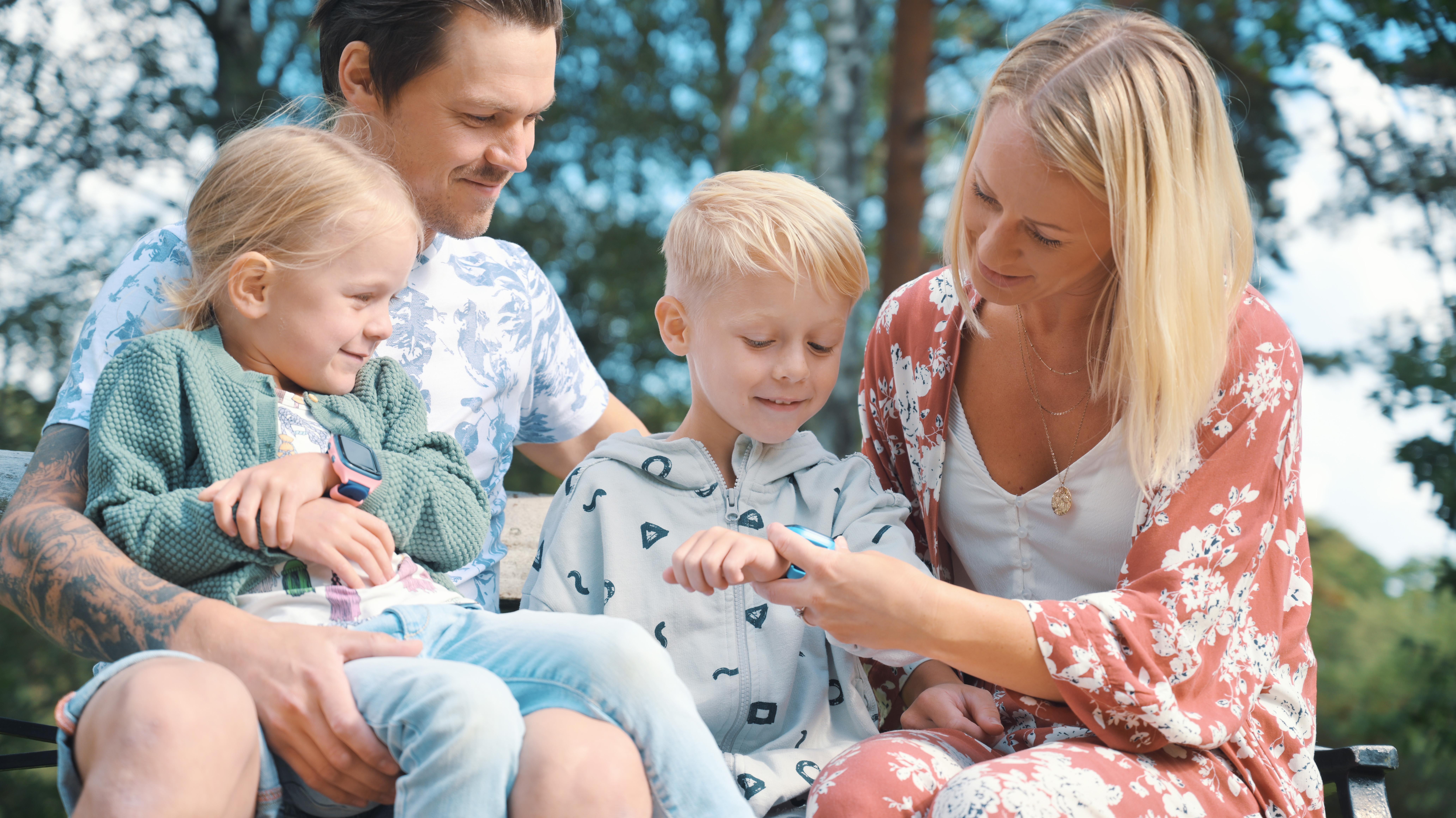 en familie på fire med to barn som har hver som xplora mobilklokke. Fra venstre er det en jente med rosa klokke, en far, en blond gutt med blå klokke og en mor helt til høyre.
