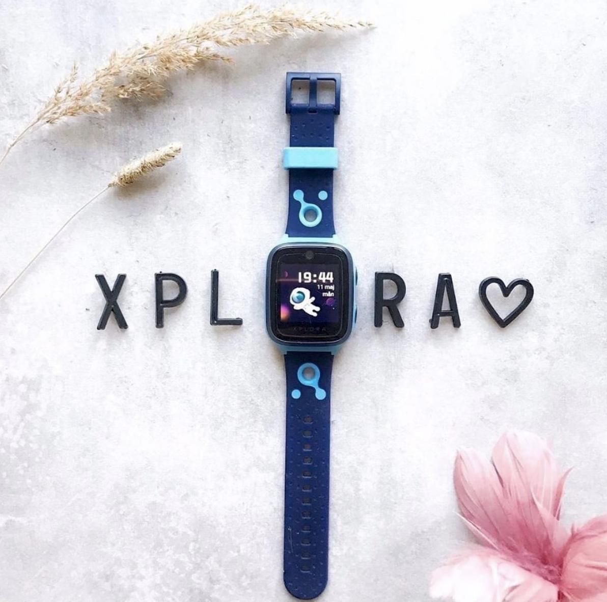 Smartklokke som ligger på et bors med bokstavene XPLORA rundt seg.